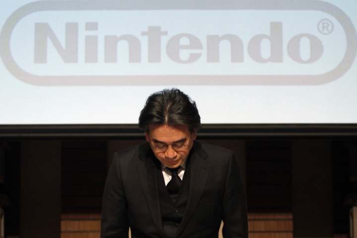 Nintendo Co President Iwata bows during their strategy and earnings briefings in Tokyo